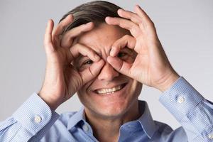 Studioaufnahme des Mannes, der mit seinen Händen eine Brillenform macht foto