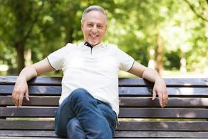 reifer Mann, der sich in einem Park entspannt foto