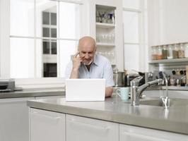 reifer Mann mit Laptop in der Küche foto