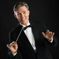fröhlicher Musikdirigent, der gestikuliert, während er mit seinem Schlagstock Regie führt foto