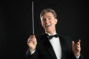 männlicher Orchesterleiter, der weg schaut, während er Regie führt foto