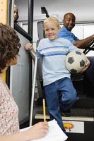 Junge, der vom Schulbus herunterkommt, während er Fußball hält foto
