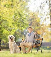 älterer Mann, der in einem Park mit seinem Hund entspannt