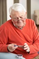 älterer Mann, der Glukose-Bluttest in seinem Haus durchführt foto