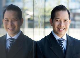 Geschäftsmann, der mit Reflexion lächelt foto