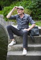 Mann sitzt am Wasser foto