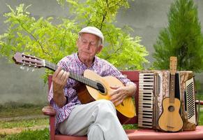 älterer Mann mit Gitarre foto