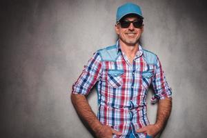 glücklicher lässiger Mann in der Jeans-Kleidung und im lächelnden Trucker-Hut