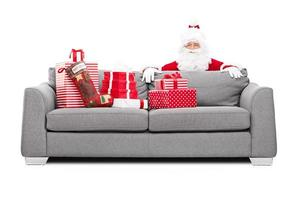 Weihnachtsmann versteckt sich hinter einem Sofa voller Geschenke