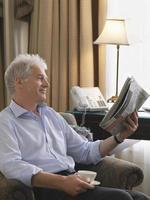 Geschäftsmann, der Zeitung im Sessel liest