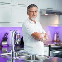 älterer Mann, der in seiner renovierten, modernen Küche steht, foto