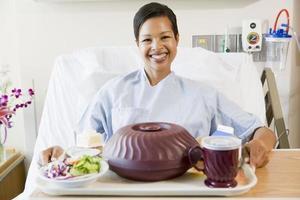 Frau sitzt im Krankenhausbett mit einem Tablett mit Essen foto