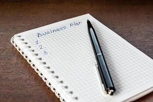 Schreiben Sie den Geschäftsplan auf und schreiben Sie ihn in das Notizbuch foto