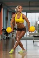 schöne Frau, die Pilatesball im Fitnesscenter tut