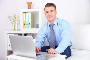 schöner junger Mann, der zu Hause am Laptop arbeitet foto