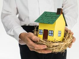 Mann hält Vogelnest mit Miniaturhaus im Inneren