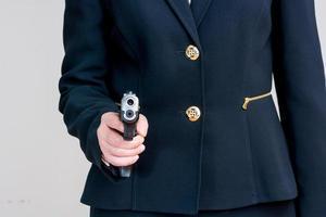 Frau zeigt mit einer Handfeuerwaffe