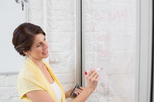 Geschäftsfrau, die Brainstorming-Ideen an Bord schreibt foto