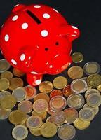 rotes Sparschwein mit Münzen foto