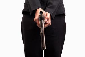 Nahaufnahme der Frau im Geschäftsanzug, die eine Waffe hält