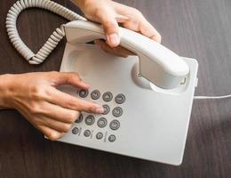 weibliche Hand, die auf einem Telefon wählt, das auf Tastatur drückt foto