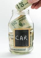 Hand Geld in Sparglas oder Bank einlegen foto