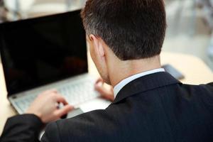 Geschäftsmann, der am Laptop arbeitet foto