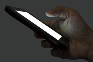 rechte Hand, die ein Smartphone nachts auf grauem Hintergrund hält foto