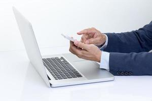 Geschäftsmannhände, die Handy mit Laptop-Computer halten foto