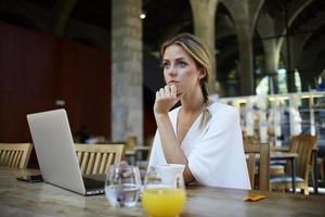 schöne verträumte Frau, die Pause zwischen der Arbeit am Netzbuch macht