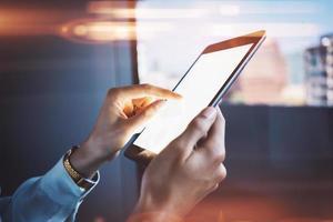 Mädchen hält Tablette in einer Hand und berührt den Bildschirm foto