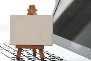 leere Leinwand und hölzerne Staffelei auf Laptop als Konzept