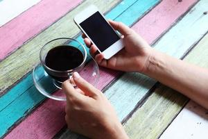 Hand mit Smartphone auf Couchtisch foto