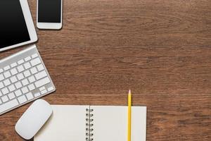 Büro Holztisch mit Notizbuch, gelbem Stift, Tablette, Keyboa foto