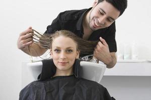 Frau lächelt mit Friseur, der ihre Haare im Salon untersucht foto