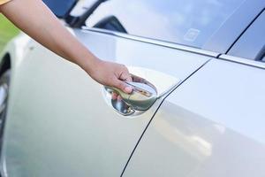 Frauenhand, die die Autotür öffnet foto