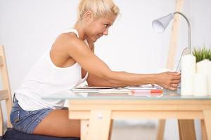 blonde Frau mit ihrem Laptop in ihrer Arbeitsseite. Seitenansicht