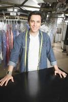 selbstbewusster männlicher Besitzer am Schalter in der Wäscherei foto