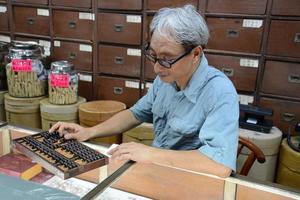 Mann im alten chinesischen Kräuterladen mit Abakus foto
