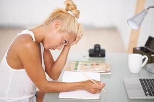 besorgte Frau, die in ihrem Schreibtisch arbeitet