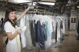 Wäschereibesitzer mit Quittung, der Kleidung überprüft foto