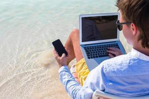 Schließen Sie herauf Telefon am Hintergrund des Computers am Strand