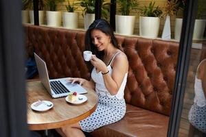 charmante Geschäftsfrau, die während des Frühstücks an ihrem Netzbuch arbeitet foto
