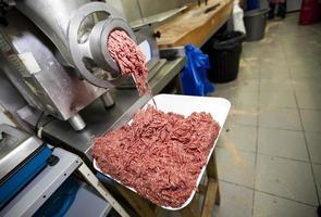 Hackfleisch fällt aus der Maschine im Behälter im Lager