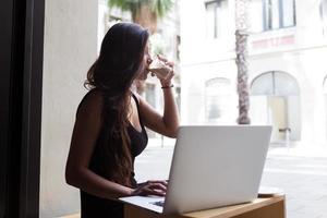 attraktive Frau, die Getränk genießt, während sie an Netzbuch im Café arbeitet foto