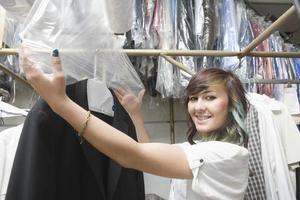 Frau, die Plastik zum chemisch gereinigten Mantel in der Wäsche setzt foto