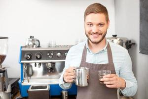 Der attraktive männliche Besitzer des Cafés arbeitet mit Freude foto