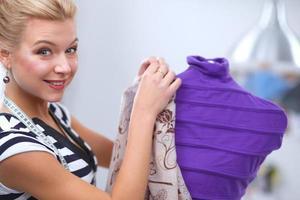 lächelnder Modedesigner, der Kleid auf Mannequin in einem Studio fixiert foto