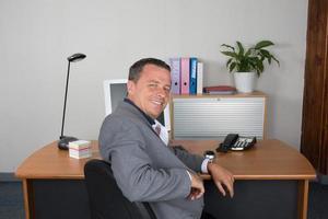 Mann bei der Arbeit, der die Kamera lächelnd betrachtet foto