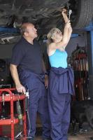 Mechaniker und Lehrling am Auto foto
